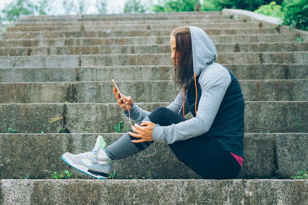 Smiling Athlete with phone relaxing on stairs in the park after workout