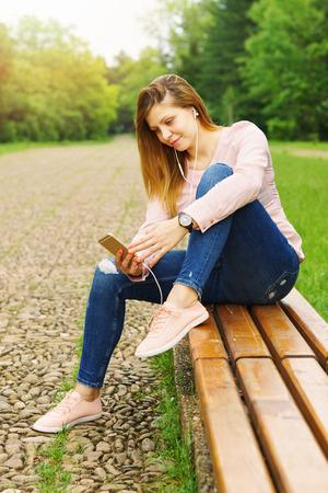Junge Frau, die draußen am intelligenten Telefon simst Standard-Bild - 80757809