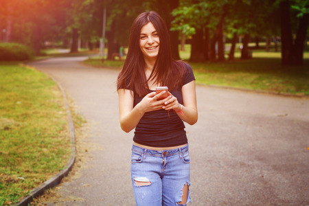 smiley face car: Modern woman looking at smartphone texting, making selfie or talking smiling happy in park. Beautiful young Caucasian, white young woman. Stock Photo