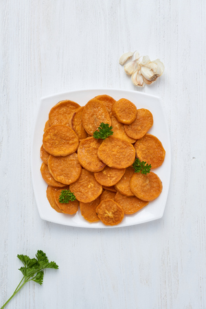 Baked sweet potatoes in white plate on a white wooden table with parsley, garlic and salt. White wooden rustic picnic table scenery from above.