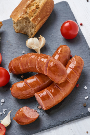 Grilled Sausages on a black stone plate on white wooden table with tomatoes, garlic, salt and pepper