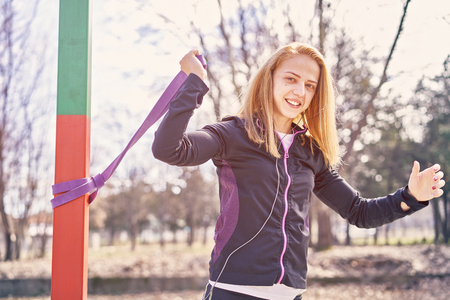 Beautiful sportswoman with smartphone exercising in park Stock Photo