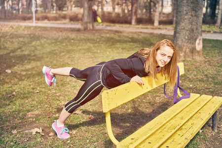 Beautiful sportswoman with smartphone exercising in park Stockfoto