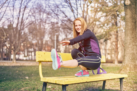 Beautiful sportswoman with smartphone exercising in park 스톡 콘텐츠