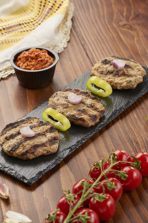 Grilled Veal minced meat with spices on black stone and wooden background
