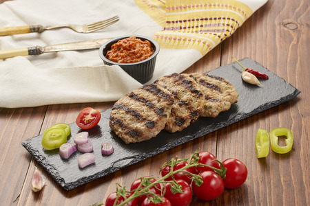 Grilled Veal minced meat with spices on black stone and wooden background 스톡 콘텐츠 - 102635706