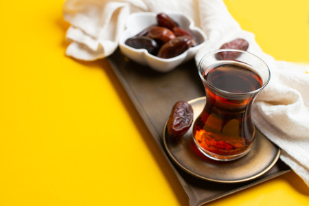 Ramadan Kareem Festival, close up of tasty dates at bowl with rosary and cup of black tea on yellow background. Zdjęcie Seryjne