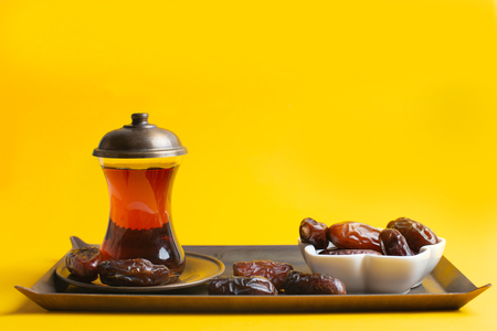 Ramadan Kareem Festival, Tasty dates at bowl with a cup of black tea on yellow background