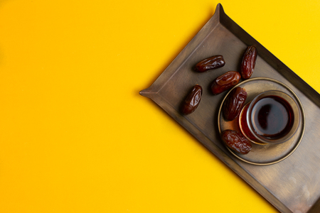 Ramadan Kareem Festive, close up of dates on plate and cup of black tea on yellow background.