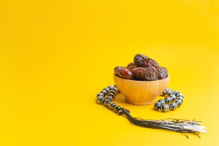 Ramadan Kareem Festival, Tasty dates at wooden bowl with rosary on yellow background Zdjęcie Seryjne