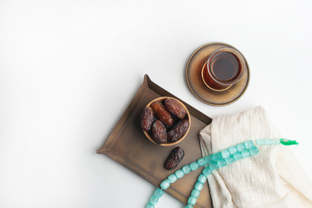 Ramadan Kareem Festival, Dates on wooden bowl with cup of black tea and rosary on white isolated background