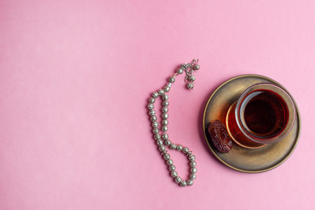 Ramadan Kareem Festival, Rosary and cup of  tea on pink background.