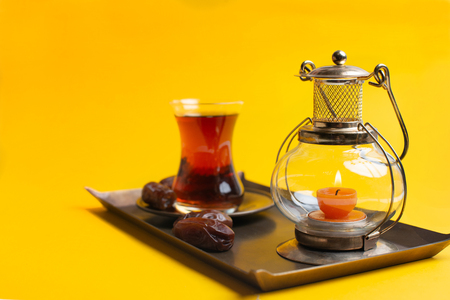 Ramadan Kareem Festive, close up of dates on plate with candle lamp and cup of black tea on yellow background