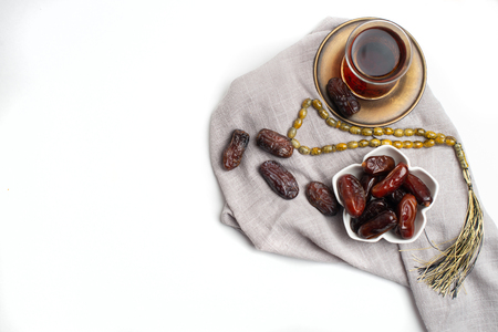 Ramadan Kareem Festive, close up of dates on bowl and cup of black tea on white background.