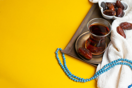 Ramadan Kareem Festival, Dates on wooden bowl with cup of black tea and rosary on yellow background