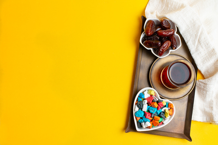 Ramadan Kareem Festival, Dates on bowl with cup of black tea and multicolor candies on yellow background