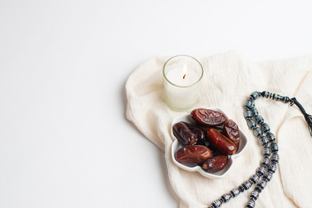 Ramadan Kareem Festival, Dates at bowl with rosary and candle the white isolated background Zdjęcie Seryjne