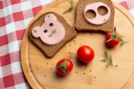 Sausage with black bread and tomate for lunch, Black bread with tomato on the wooden background, Tomates with black bread