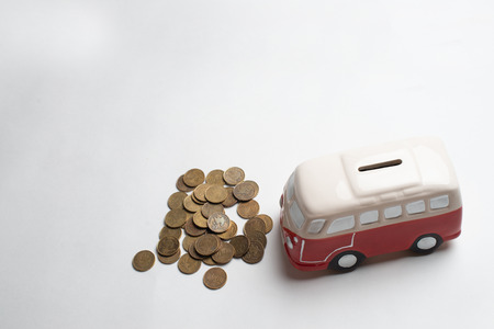 Red bus moneybox with coins. Stock Photo
