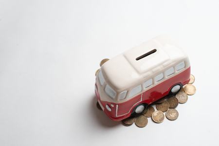 Red bus moneybox with coins.