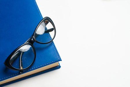 Notebook with glasses and pen, Book with glasses, Blue notebook with glasses, Book with cup of tea, working with glasses and pen, write to notebook 스톡 콘텐츠