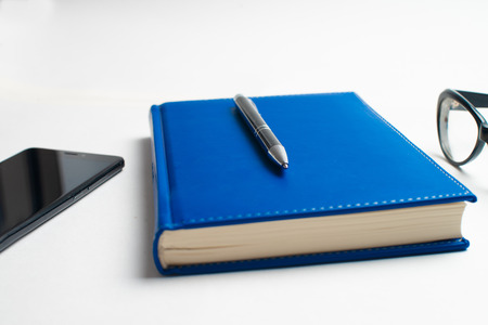 Notebook with glasses and pen, Book with glasses, Blue notebook with glasses, Book with cup of tea, working with glasses and pen, write to notebook Фото со стока