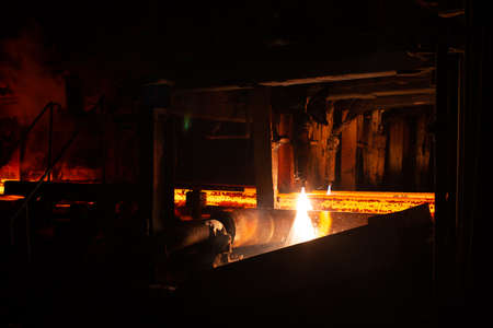 Hot red steel billets at torch cutting. Background of the blacksmith and metallurgical industry. Фото со стока
