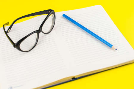 Black eye glasses and notepad planner with pencil on yellow background. Flat lay. Copy space. Workplace in the office.