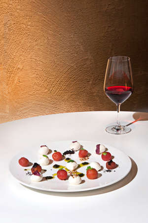 Mini mozzarella cheese platter red wine. Red wine and cheese plate with wall background.
