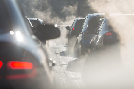 Blurred silhouettes of cars surrounded by steam from the exhaust pipes Stock Photo