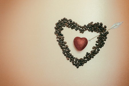 Red heart inside heart of coffee beans. Piercing Cupid arrow. Place for text