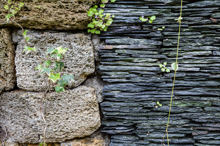 contradict: Junction of walls with two different textures. Layers of uneven black stone side by side to grungy pumice bricks. Natural background and texture for design