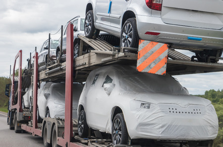 New cars for sale on bunk platform of truck