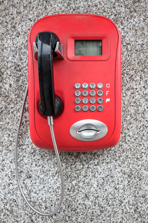 Red public telephone with black handset on the granite wall