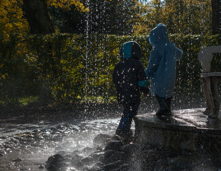 Children silhouettes under the rain of the fountain. Drops and splashes of water illuminated by sunlight