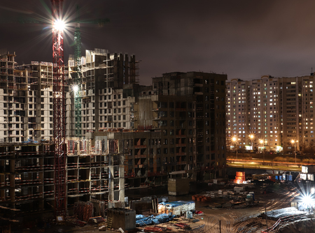 Construction site at night. Building under construction lighted by bright spotlights