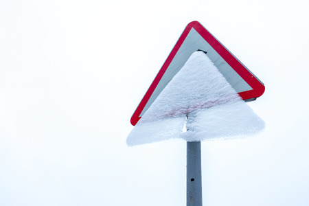 Road sign covered with snow. Icy crust obscures symbol on traffic sign. White background