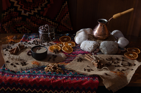 Ð¡offee table with the cezva on sand and patterned tablecloth in Oriental style. Scattered coffee beans and spices