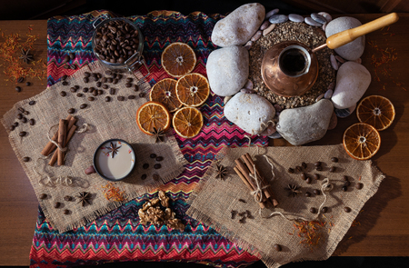 Ð¡offee table with the cezva on sand and patterned tablecloth in Oriental style. Scattered coffee beans and spices. Top view