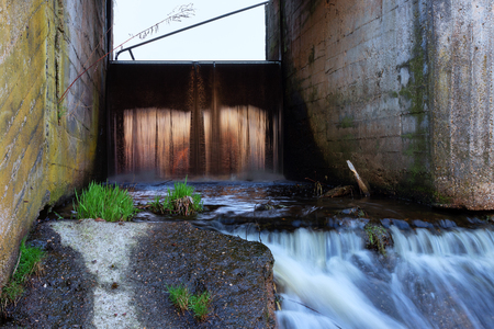 Concrete structure of the old river dam. Waterfall at sunset. Water blurred by long exposure 版權商用圖片