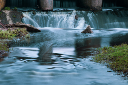 Part of the concrete structure of the river dam. Water blurred by long exposure