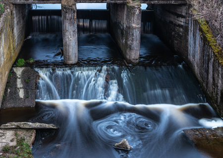 Concrete structure of the old river dam. Water blurred by long exposure 版權商用圖片
