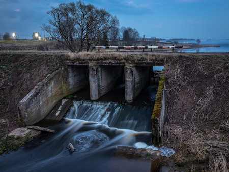 Old river dam in the evening. Water blurred by long exposure