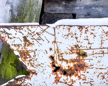 Scratched metal sheet and rusty holes background. Wooden board covered with green moss. Texture for design