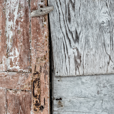 Old wooden door with peeling brown paint. Plywood sheets with wood pattern. Two different textures. Space for text