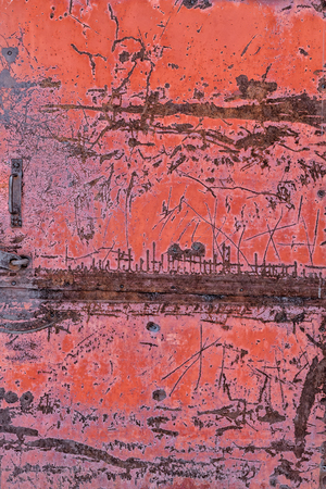 Old metal door with peeling red paint. Rusty scratched metal surface