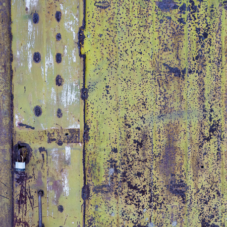 Old metal door with peeling green paint. Rusty metal surface. Spotted pattern