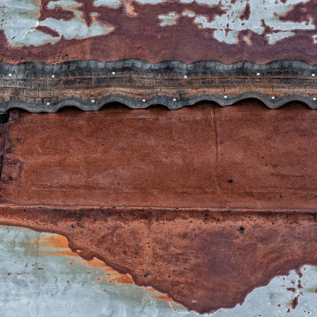 Rusty metal surface with nailed rubber tape. Space for text