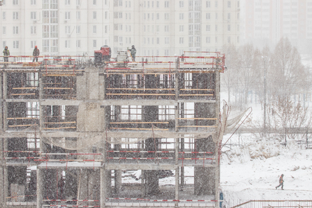Part of a building under construction in a snowfall. Workers on construction site 版權商用圖片