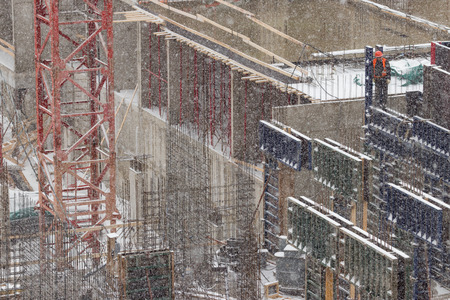 Building under construction in a snowfall close-up. Worker stands on the edge of a concrete structure